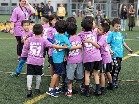 Elementary students playing on the athletic field