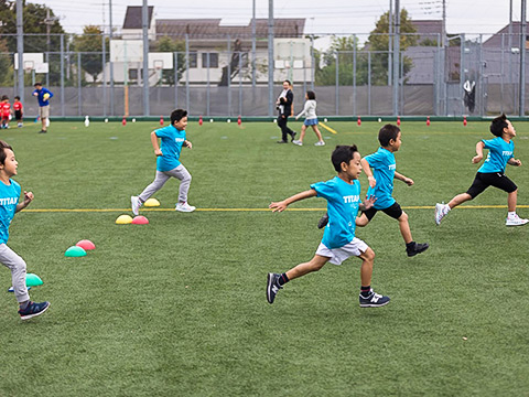 Elementary students running on the athletic field