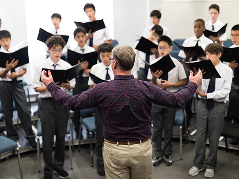Students under the direction of the choir master